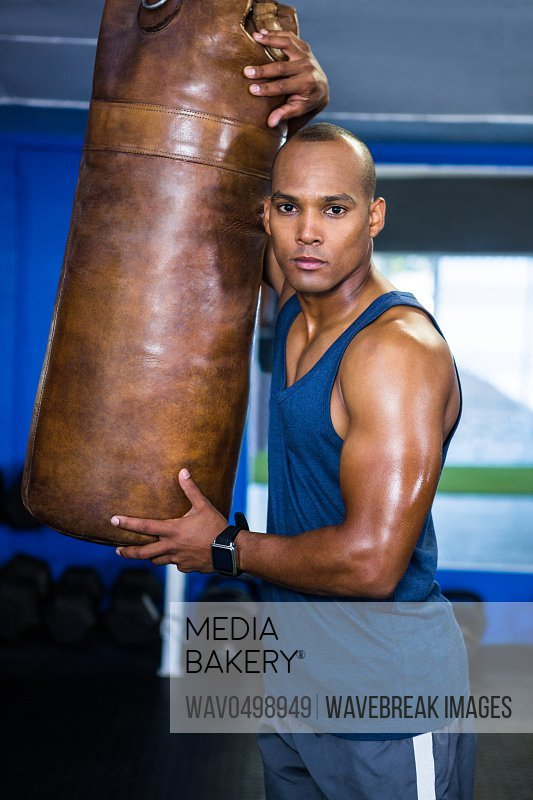 Portrait of confident male athlete standing by punching bag in gym