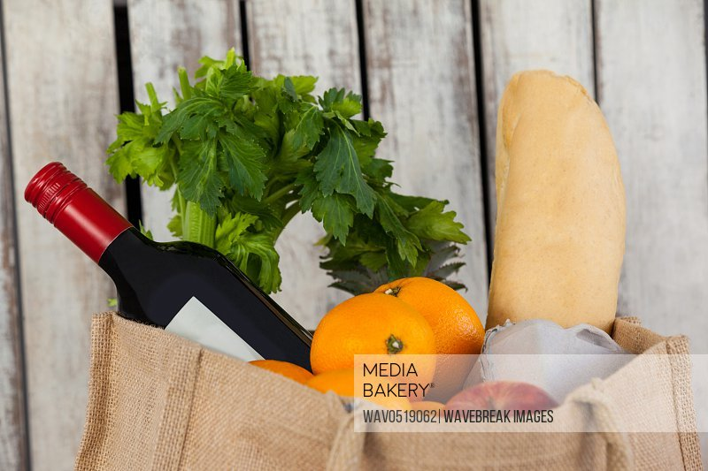 Wine bottle fruits and vegetables with bread loaf in grocery bag
