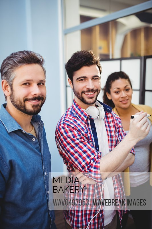 Portrait of confident young business partners during meeting at creative office