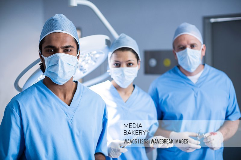 Portrait of surgeons holding surgical tool in operation room at the hospital