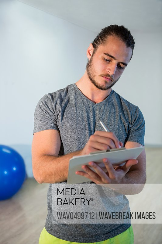Fitness trainer writing on clipboard in fitness studio