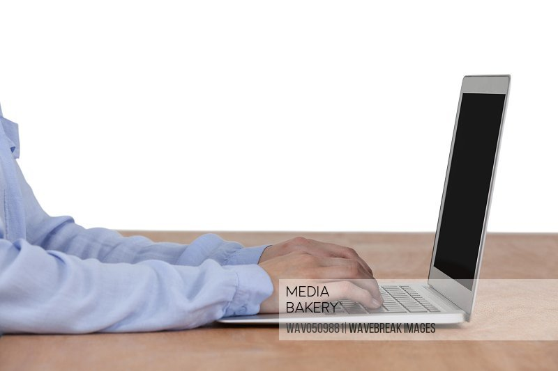 Businesswoman sitting at desk and using laptop against white background