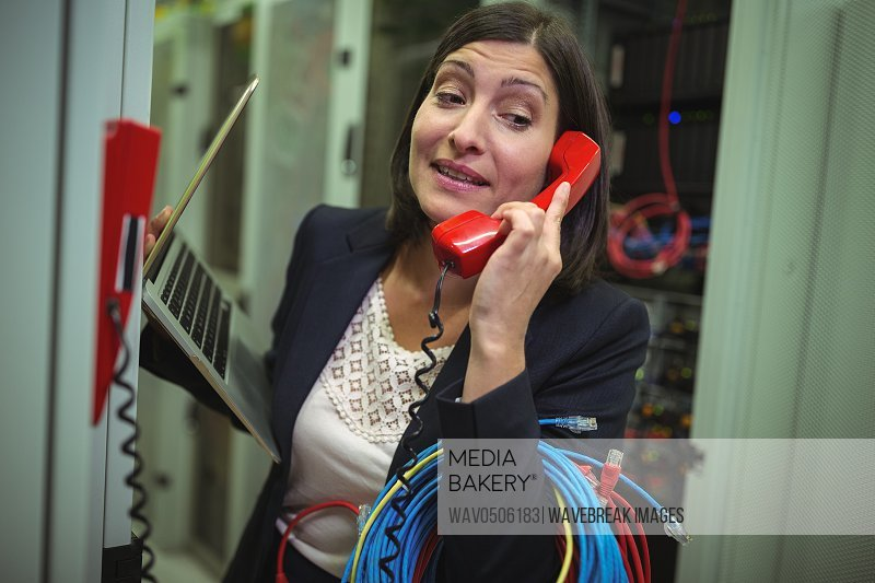 Technician talking on phone while analyzing server in server room