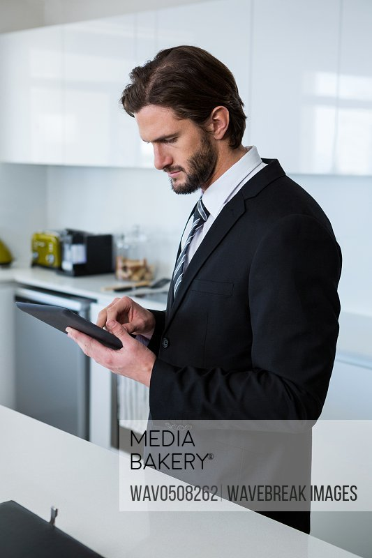 Businessman using digital tablet in kitchen at home