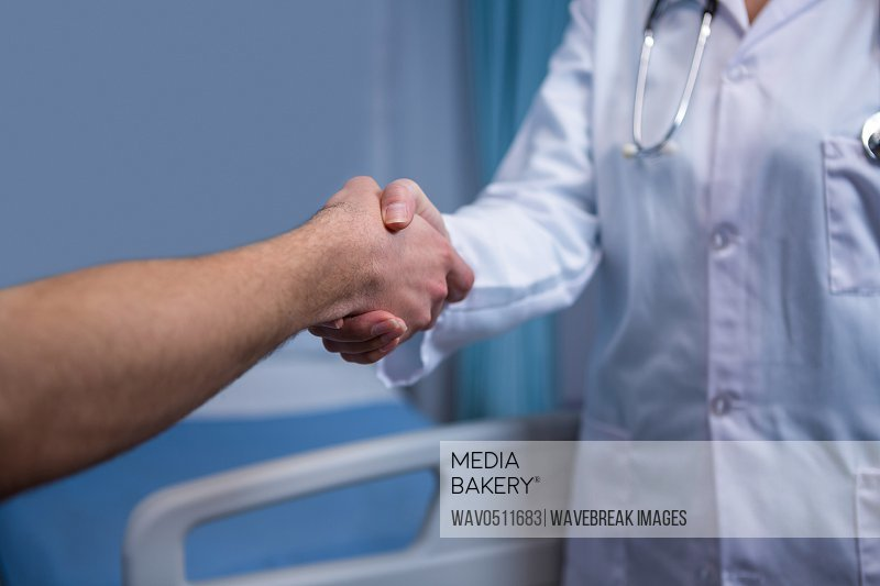 Mid section of nurse and doctor shaking hands at hospital