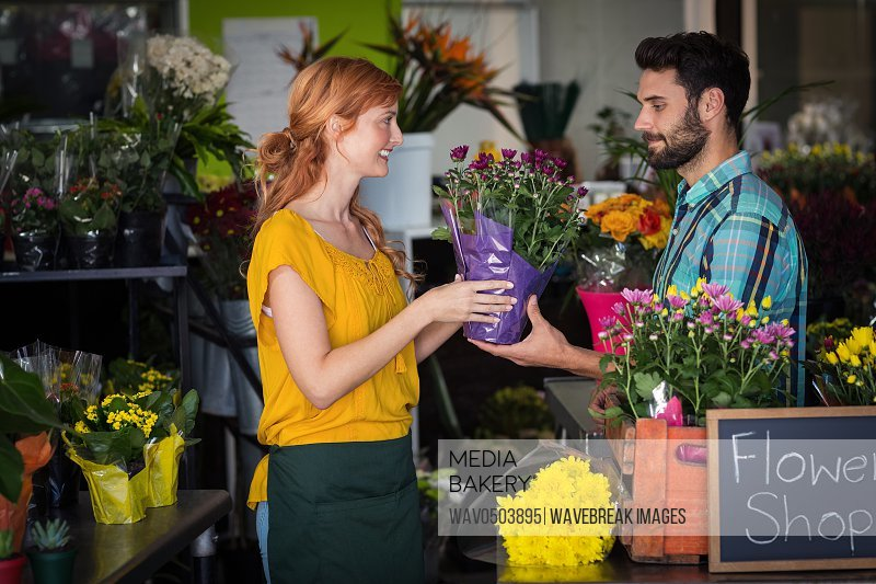 Female florist giving bouquet of flower to man in the flower shop