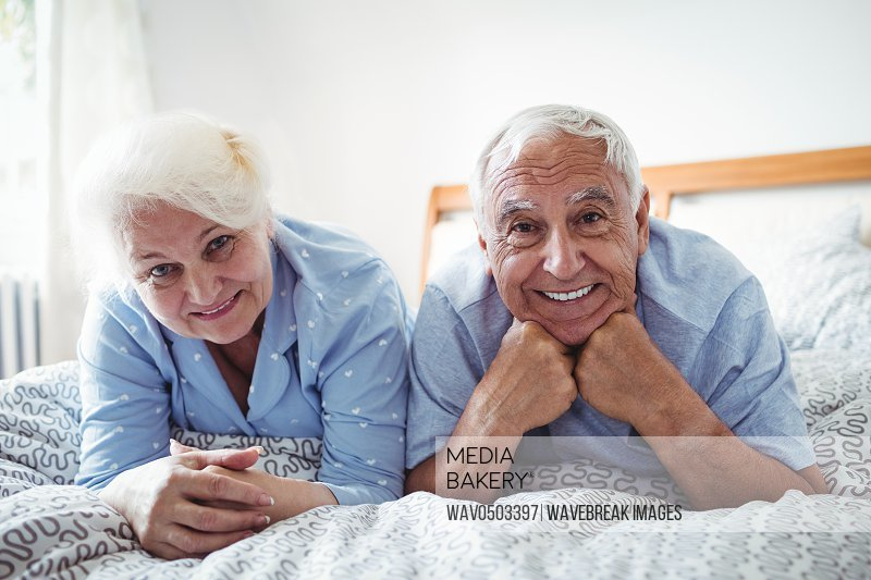 Portrait of senior couple relaxing on bed in bedroom