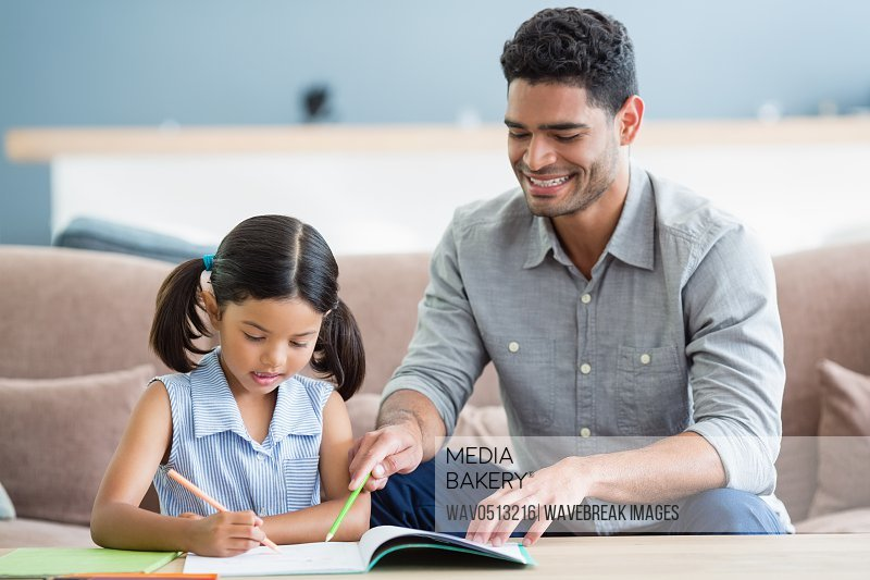 Father assisting her daughter in doing her homework