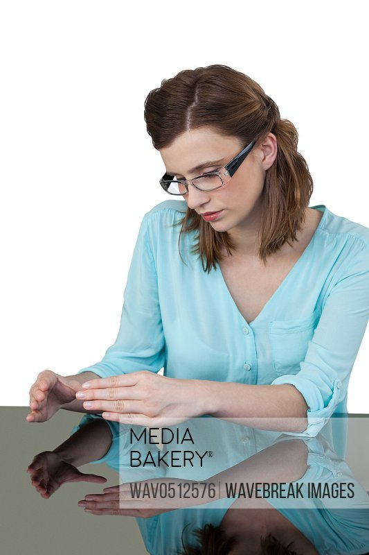 Businesswoman sitting at desk and gesturing against white background