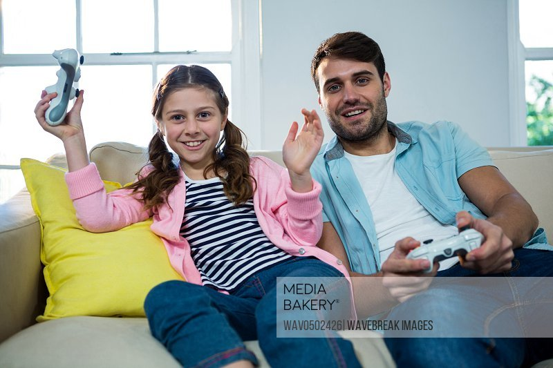 Father and daughter playing video game in the living room at home