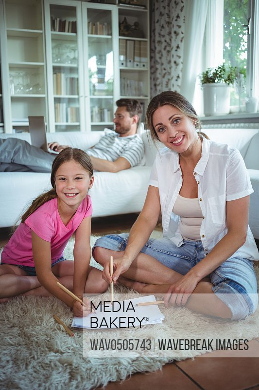 Mother and daughter sitting on the floor and drawing while father using laptop in background