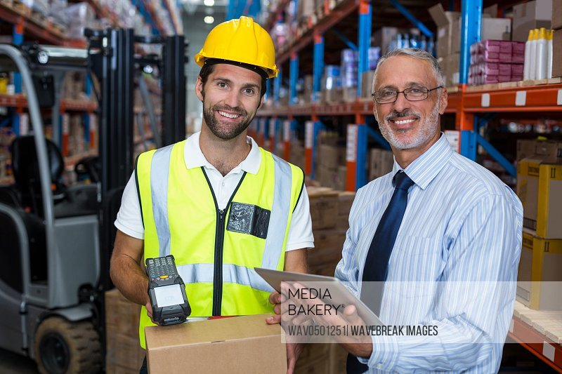 Warehouse manager holding digital tablet while male worker scanning barcode in warehouse