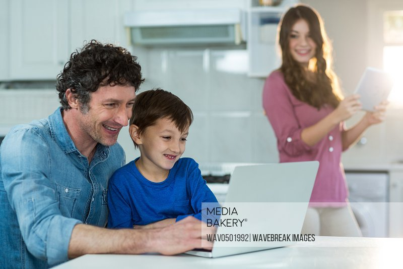 Family using digital tablet and laptop at home