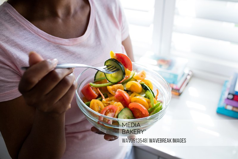 Mid section of woman having salad