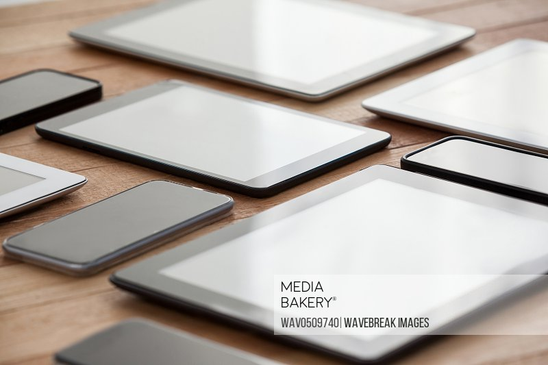 Close-up of mobile phones and digital tablets on table