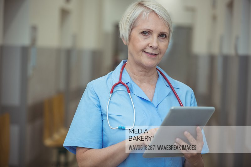 Portrait of female surgeon using digital tablet in corridor
