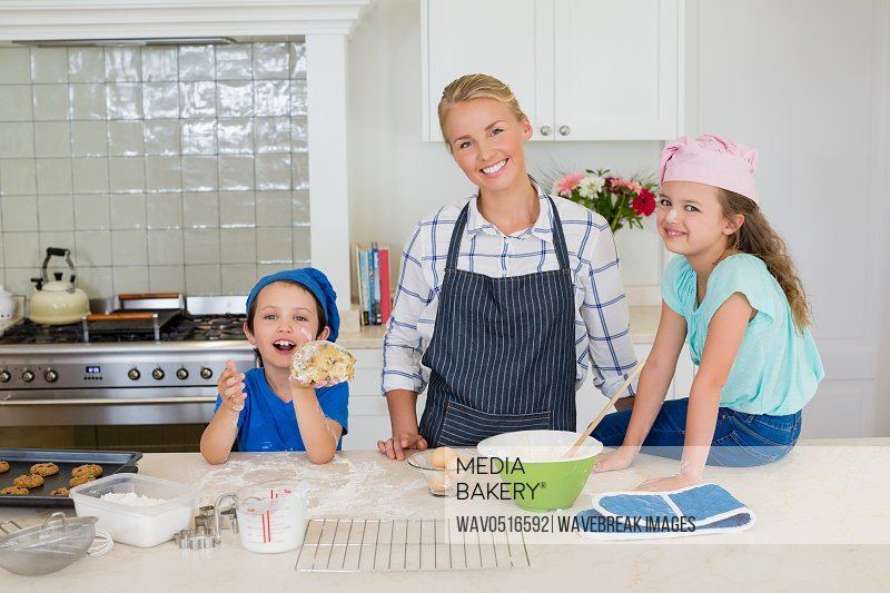 Smiling mother and kids standing in kitchen