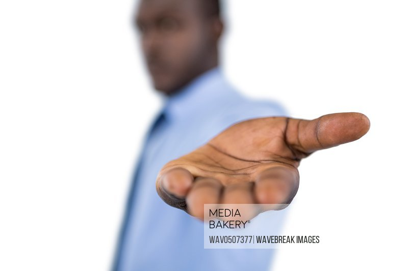 Businessman showing his hand against white background