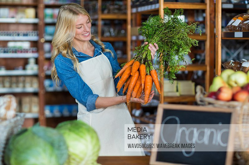 Smiling female staff holding bunch of carrots in organic section of super market