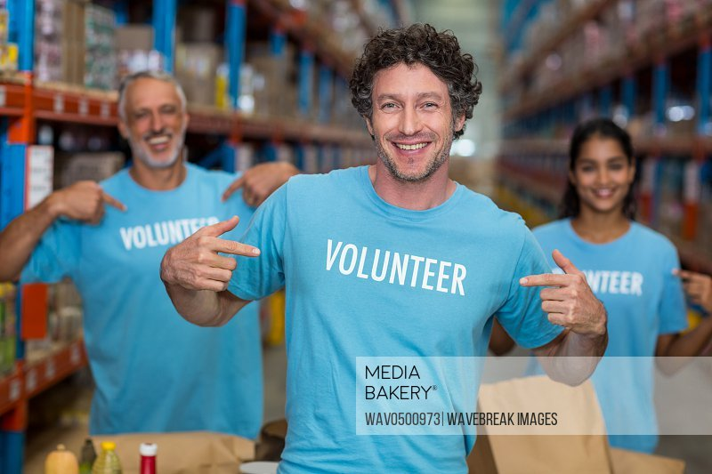 Portrait of volunteers pointing at t-shirt in warehouse