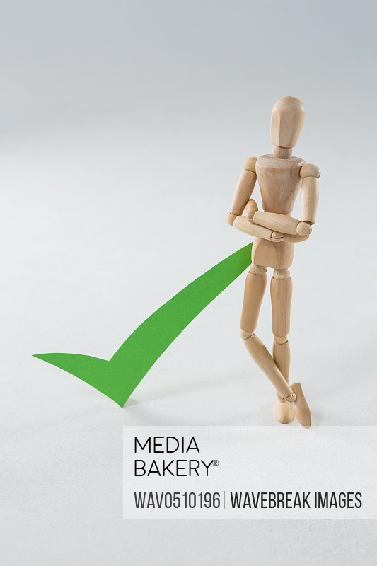Wooden figurine with green check mark on wooden background
