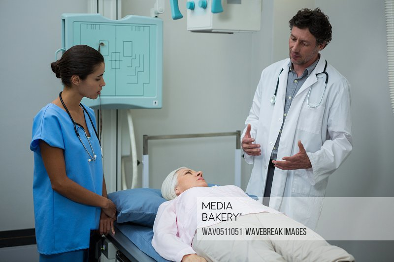 Doctors interacting with patient in hospital