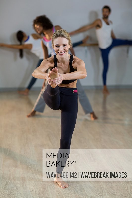Portrait of woman performing stretching exercise in fitness studio