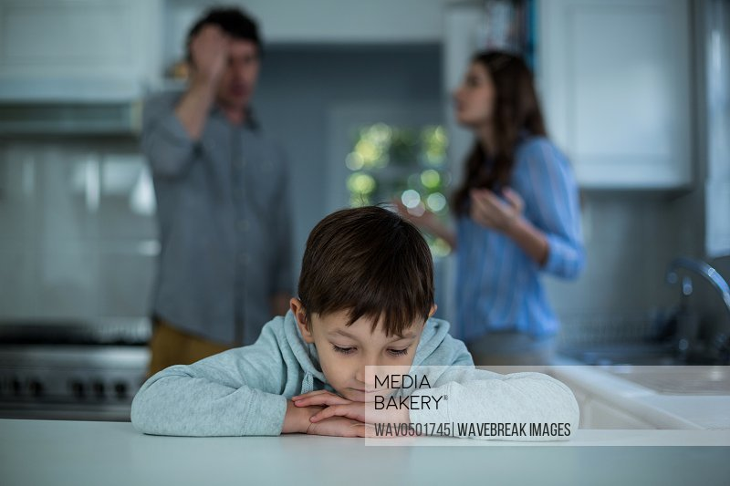 Upset boy sitting while couple having argument in background at kitchen