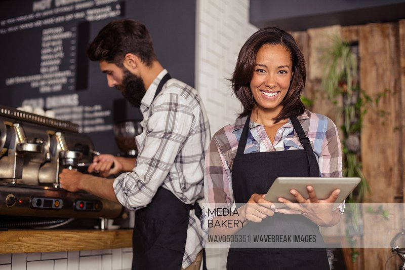 Waitress using digital tablet while waiter preparing coffee in background at cafA?