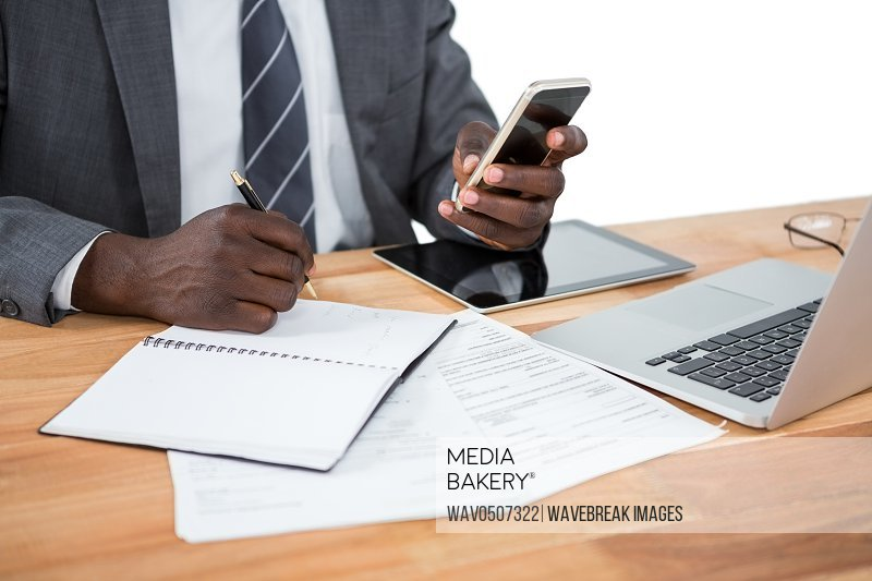 Mid section of businessman using phone and other multimedia devices at desk