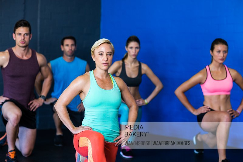 Determined male and female athletes exercising in fitness studio