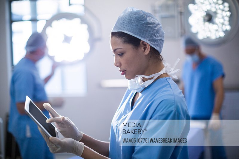 Female surgeon using digital tablet in operation room at hospital