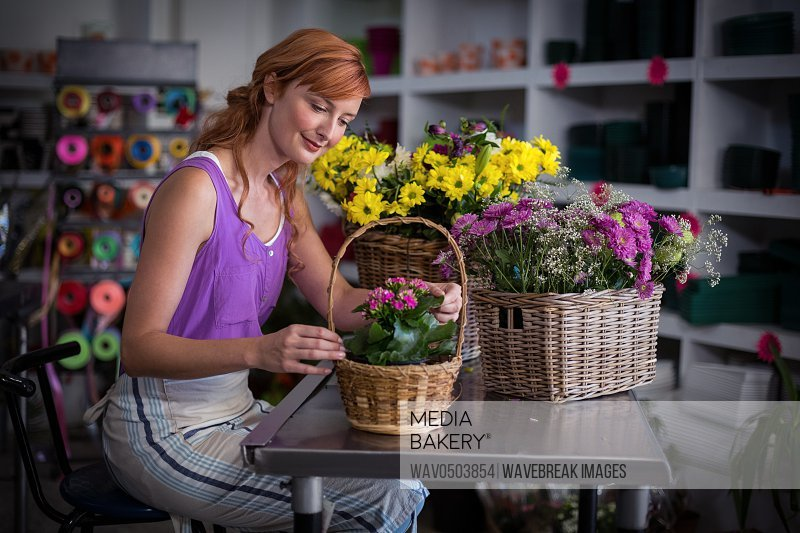 Female florist preparing basket of flowers in the shop