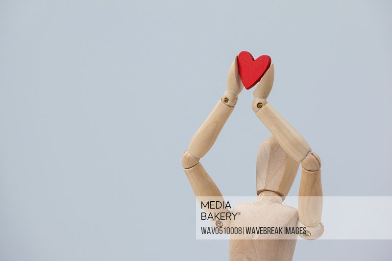 Wooden figurine holding a red heart on top against white background