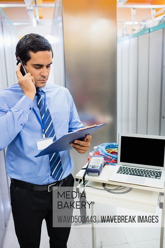 Technician dictating checklist report on mobile phone in server room
