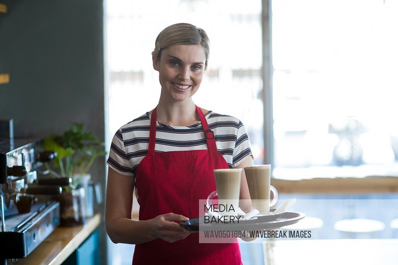 Portrait of smiling waitress holding cup of cold coffee at counter in cafe