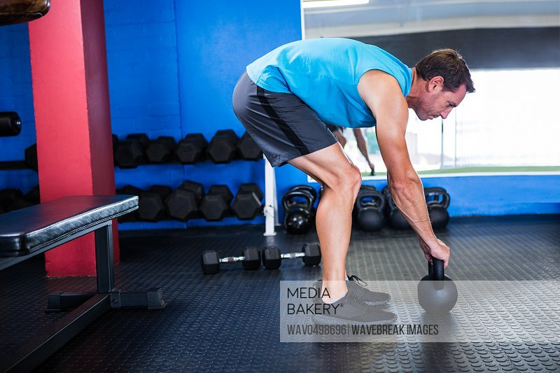 Side view of athlete with kettlebell while exercising in gym