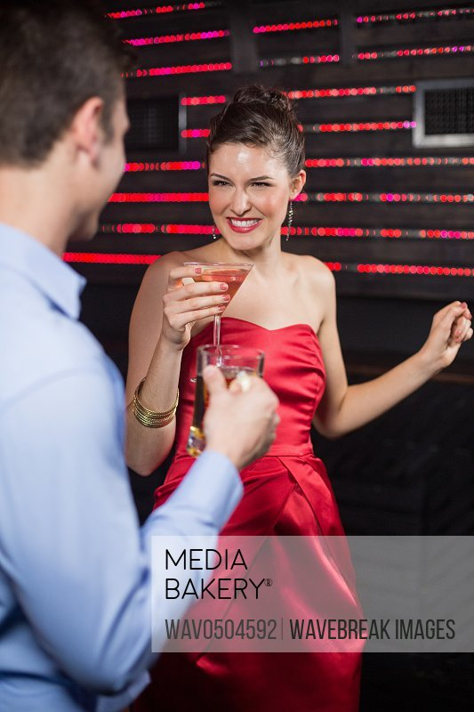 Smiling couple holding glass of beer and cocktail while dancing at bar