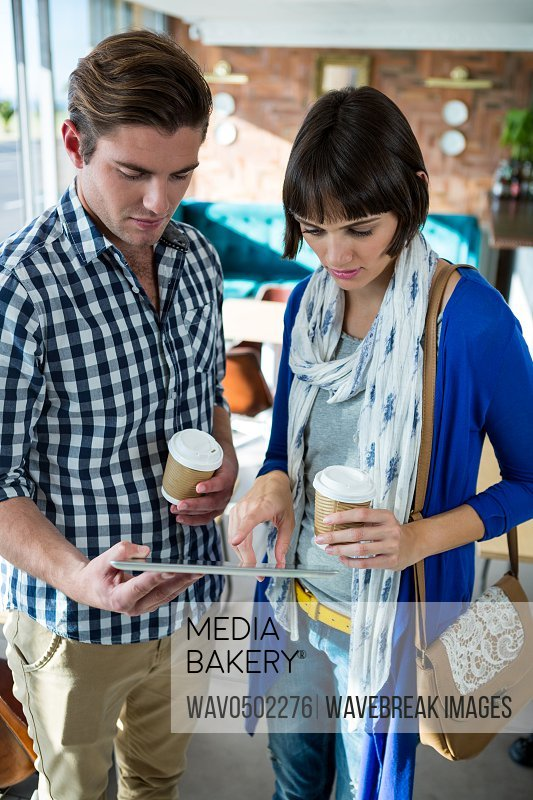Couple with coffee cups using a digital tablet in coffee shop