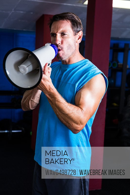 Fitness instructor shouting through megaphone in gym