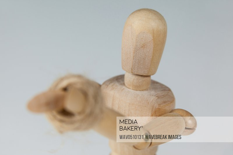 Hands of wooden figurine tied with a rope against white background