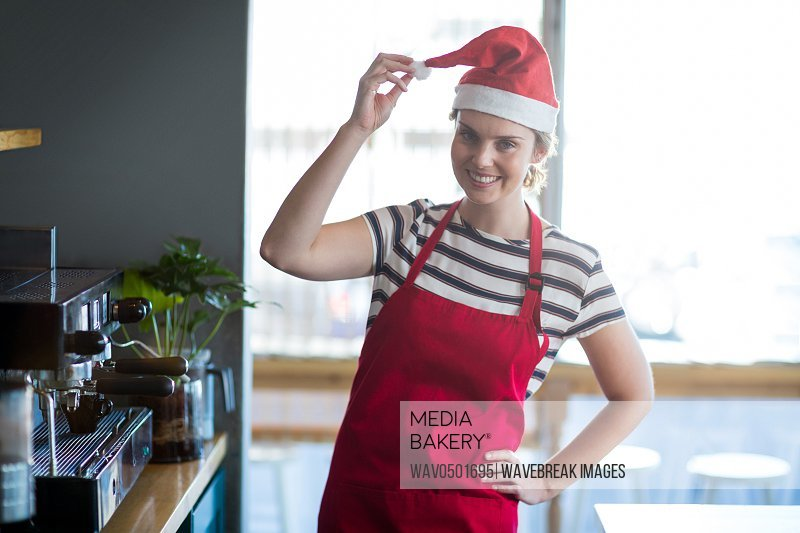Portrait of waitress in santa hat standing with hand on hip at cafA?