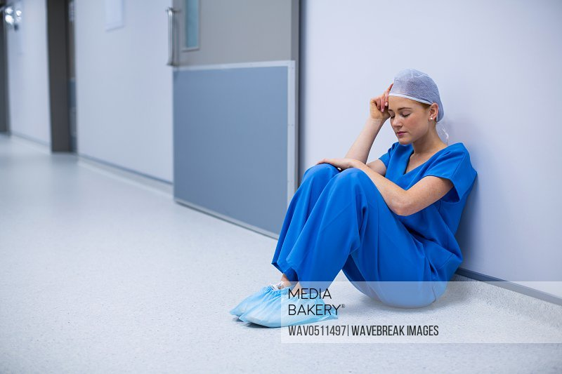 Tensed female nurse sitting in corridor of hospital