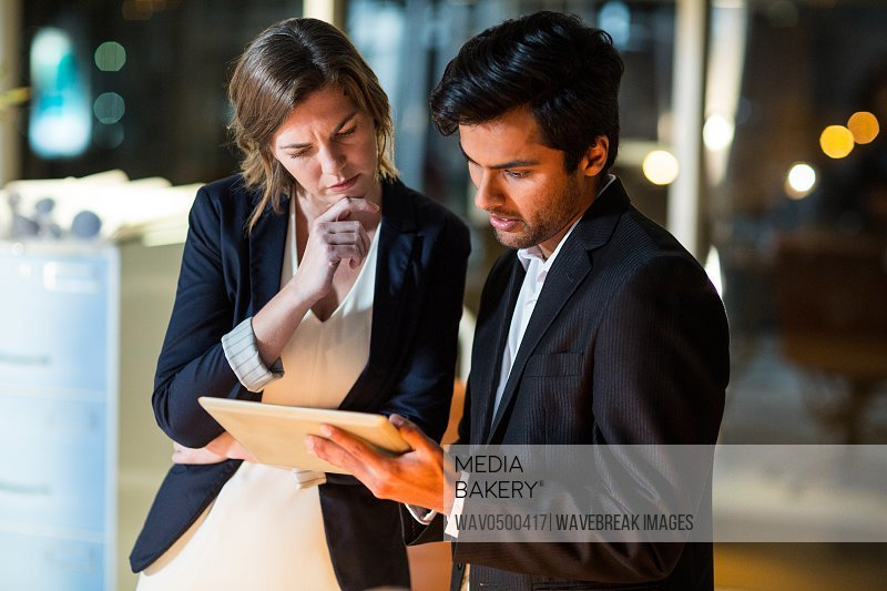 Businessman discussing with colleague over digital tablet in the office