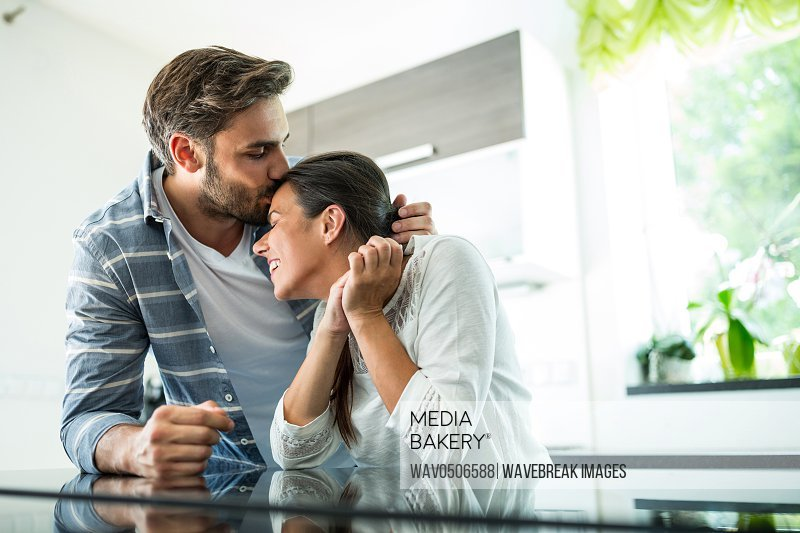 Man kissing on woman forehead at home