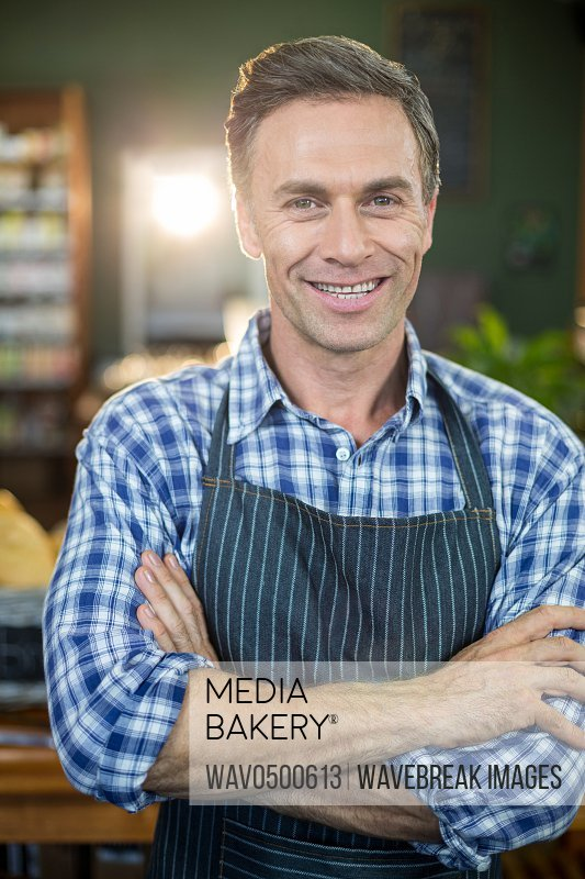 Portrait of smiling male staff standing in supermarket with his hands crossed