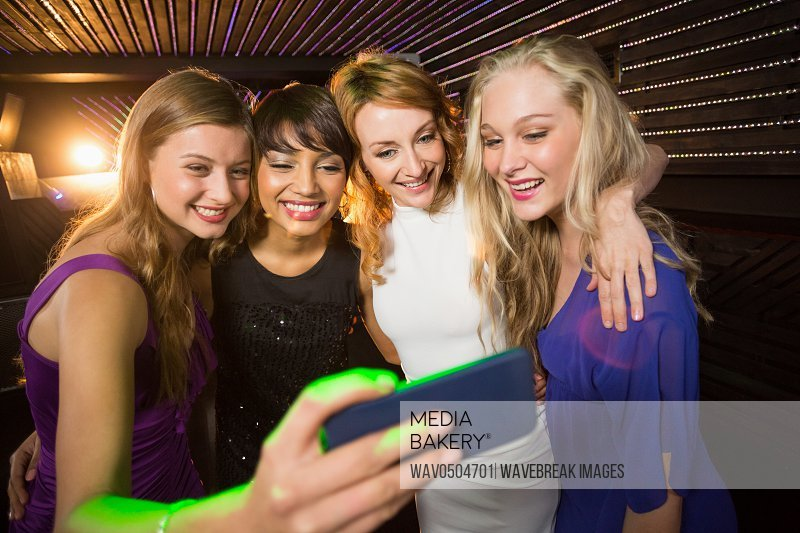 Smiling female friends taking a selfie from mobile phone in bar