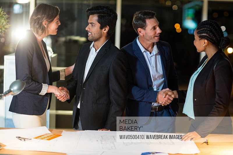Group of businesspeople shaking hands with each other in the office