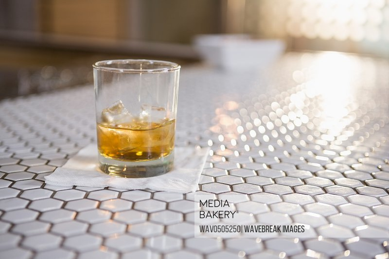 Glass of whisky on bar counter in bar