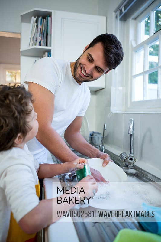 Son helping father in washing utensils in the kitchen sink